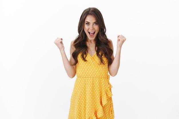 Szczęśliwa ambitna śliczna brunetka wiwatująca świętująca zwycięstwo, zaciskająca ręce, radośnie pompująca pięścią, osiągająca sukcesy, dobre wieści, radośnie się uśmiechająca, wygrywająca i ciesząca się z doskonałych osiągnięć