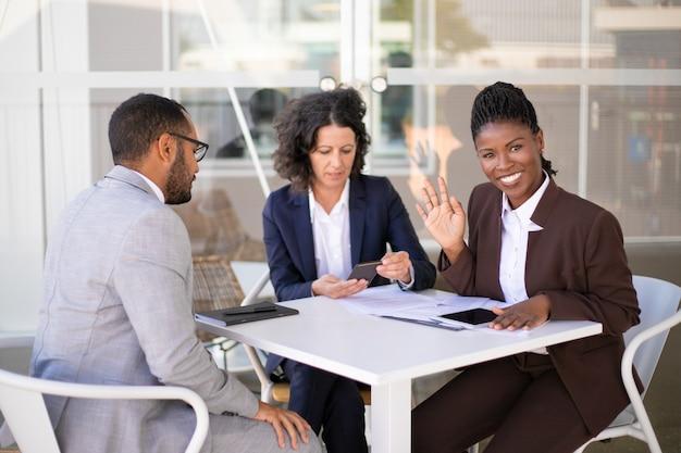 Szczęśliwa amerykanin afrykańskiego pochodzenia biznesowa kobieta macha cześć