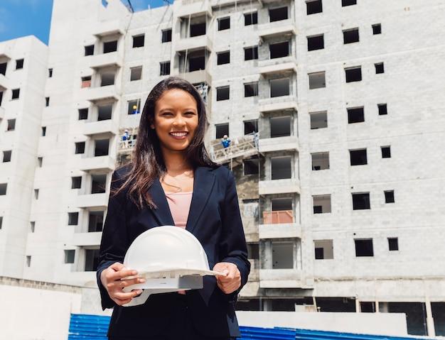 Szczęśliwa amerykanin afrykańskiego pochodzenia dama trzyma zbawczego hełm blisko budynku w budowie