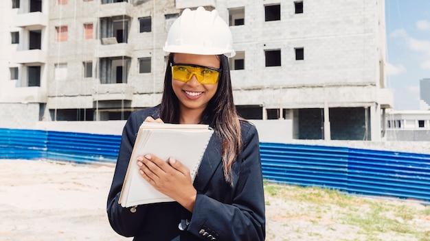 Szczęśliwa amerykanin afrykańskiego pochodzenia dama w zbawczego hełma writing w notatniku blisko budynku w budowie
