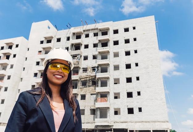 Szczęśliwa amerykanin afrykańskiego pochodzenia dama w zbawczym hełmie i eyeglasses blisko budynku w budowie