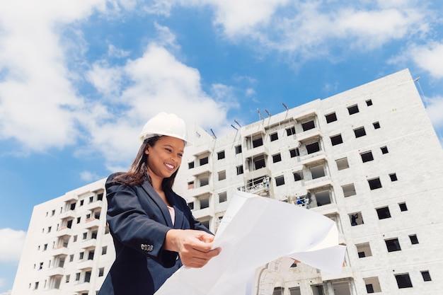 Szczęśliwa amerykanin afrykańskiego pochodzenia dama w zbawczym hełmie z papierowym planem blisko budynku w budowie