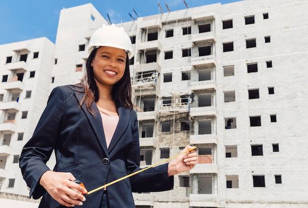 Szczęśliwa amerykanin afrykańskiego pochodzenia dama w zbawczym hełmie z pomiarową taśmą blisko budynku w budowie