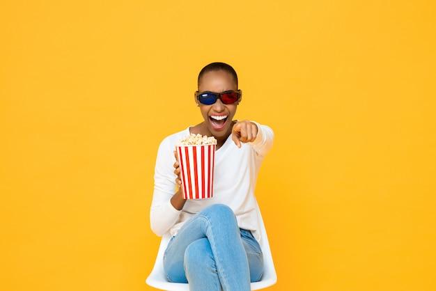 Szczęśliwa amerykanin afrykańskiego pochodzenia kobieta śmia się z okularami 3d i popkornem podczas gdy oglądający film na kolor żółty ścianie