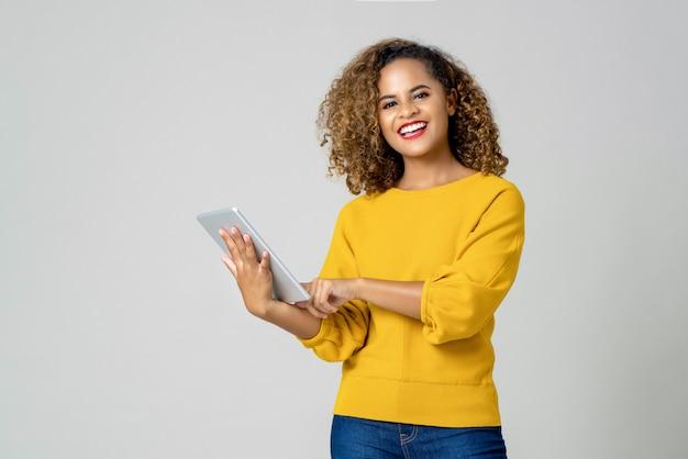 Szczęśliwa amerykanin afrykańskiego pochodzenia kobieta używa jej urządzenie elektroniczne