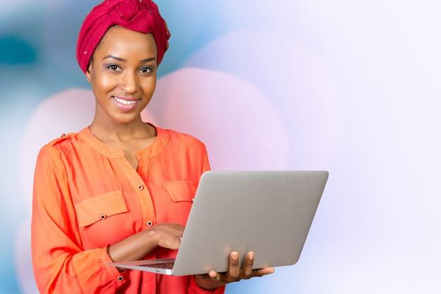 Szczęśliwa amerykanin afrykańskiego pochodzenia kobieta z laptopem