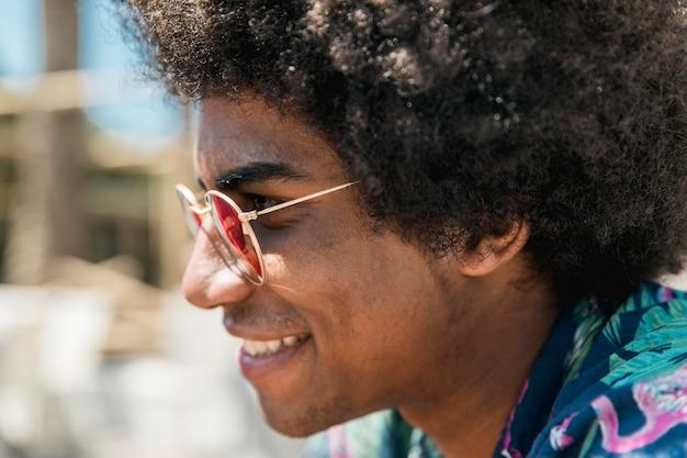 Szczęśliwa amerykanin afrykańskiego pochodzenia samiec w okularach przeciwsłonecznych