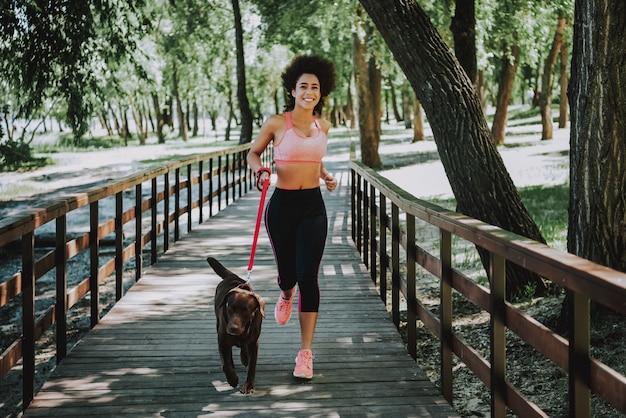 Szczęśliwa amerykańska kobieta jogging na kładce