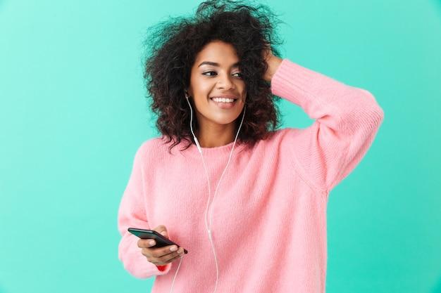 Szczęśliwa amerykańska kobieta w ubranie, słuchanie muzyki na telefon komórkowy przez białe słuchawki, odizolowane na niebieskiej ścianie