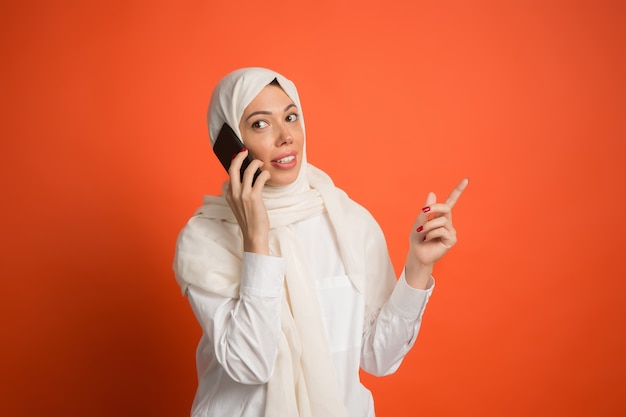 Szczęśliwa arabska kobieta w hidżabie z telefonem komórkowym.