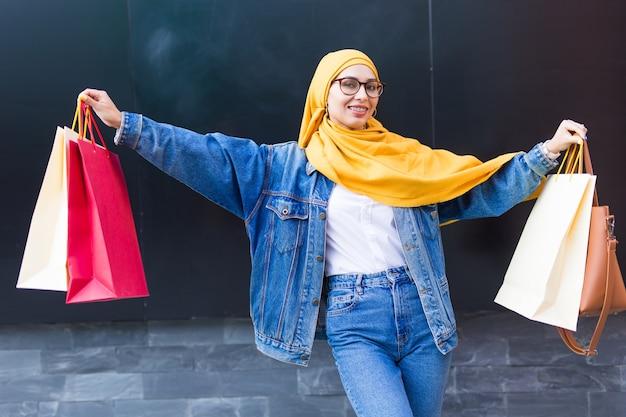 Szczęśliwa arabska muzułmańska dziewczyna z torby na zakupy