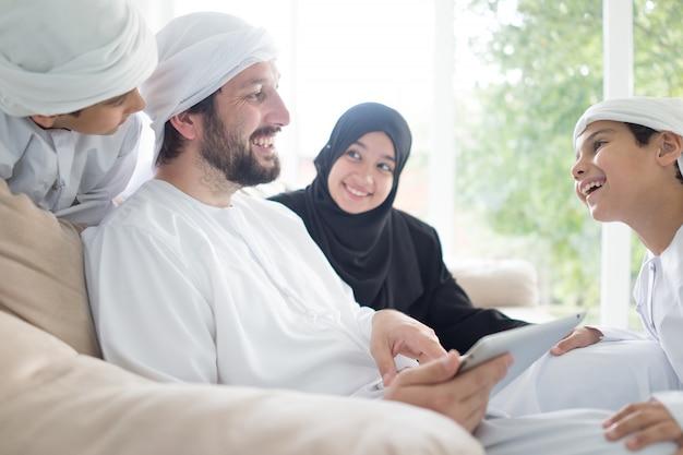 Szczęśliwa arabska rodzina ma zabawę w domu na kanapie używać pastylkę