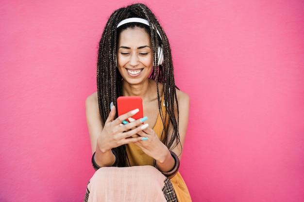 Szczęśliwa artystyczna wpływowa kobieta słuchająca muzyki z playlisty na różowym tle - skup się na twarzy