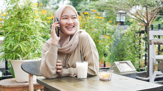 Szczęśliwa asia hidżab kobieta za pomocą inteligentnego telefonu i dzwoniąc, siedząc w kawiarni