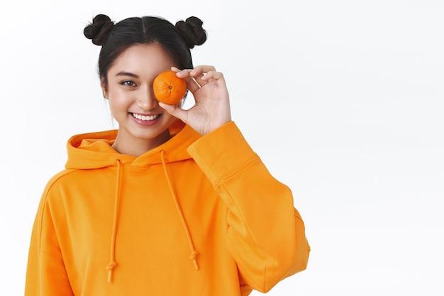 Szczęśliwa atrakcyjna azjatycka kobieta z uroczymi bułeczkami do włosów, pomarańczową bluzą z kapturem, trzymającą jedną mandarynkę nad okiem i uśmiechniętą kamerą, koncepcja zdrowego stylu życia, naturalny makijaż, biała ściana stoiska