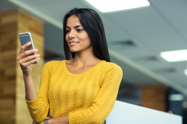 Szczęśliwa atrakcyjna bizneswoman używająca smartfona w biurze