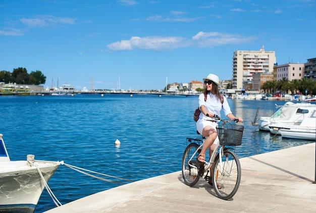 Szczęśliwa atrakcyjna dziewczyna w okularach przeciwsłonecznych iz plecakiem jedzie na rowerze wzdłuż kamienistego chodnika