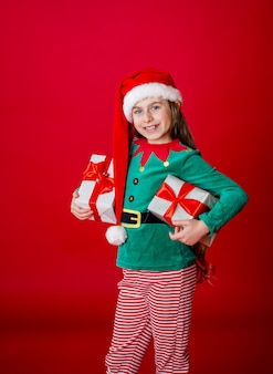 Szczęśliwa atrakcyjna dziewczyna z prezentami w stroju świętego mikołaja elfa pomocnika na jasny czerwony