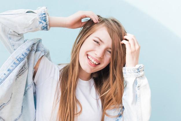 Szczęśliwa atrakcyjna kobieta jest ubranym kurtkę drelichową pozuje blisko błękitnego tła