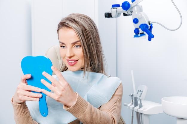 Szczęśliwa atrakcyjna kobieta patrząc na jej zęby w lustrze. zadowolony pacjent z opieki stomatologicznej lub wybielania do leczenia stomatologicznego.
