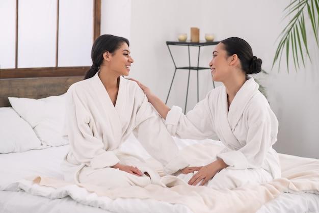 Szczęśliwa atrakcyjna kobieta, patrząc na swojego partnera, będąc razem z nią w salonie spa