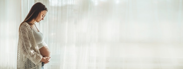 Szczęśliwa atrakcyjna kobieta w ciąży stojąca w pobliżu okna i trzymając jej brzuch. koncepcje ciąży i rodziny