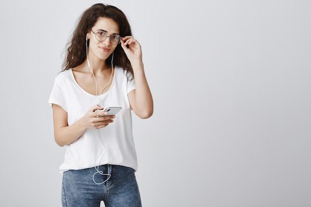 Szczęśliwa atrakcyjna kobieta za pomocą telefonu komórkowego, słuchanie muzyki w słuchawkach