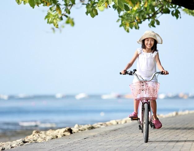 Szczęśliwa atrakcyjna mała dziewczynka jest ubranym kapeluszowego jeździeckiego bicykl plenerowego