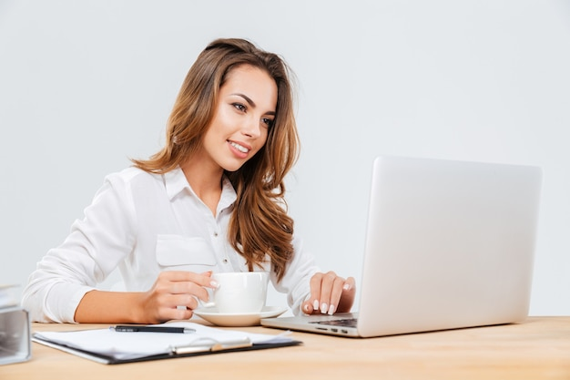 Szczęśliwa atrakcyjna młoda bizneswoman pije kawę i używa laptopa na białym tle