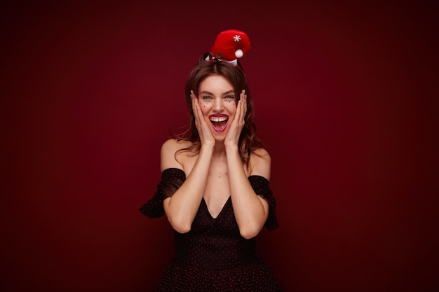Szczęśliwa atrakcyjna młoda brązowowłosa dama ubrana w elegancką sukienkę z czerwonymi kropkami i santa hat pozowanie, uśmiechając się szeroko z podekscytowaną twarzą