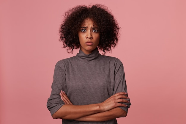 Szczęśliwa atrakcyjna młoda ciemnoskóra brunetka kobieta z krótkimi kręconymi włosami pozuje w swetrze z szarym gardłem, szeroko się uśmiecha i trzyma podniesione ręce na głowie