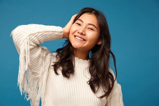 Szczęśliwa atrakcyjna młoda kobieta długowłosy ubrana w biały sweter z dzianiny