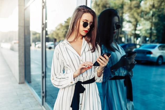 Szczęśliwa atrakcyjna młoda kobieta patrzeje smartphone ekran w okularach przeciwsłonecznych