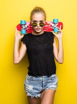 Szczęśliwa atrakcyjna młoda kobieta siedzi na deskorolce na żółtym tle w okularach przeciwsłonecznych