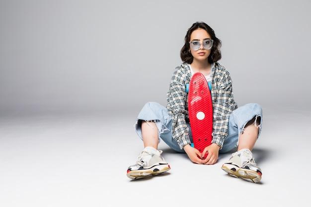 Szczęśliwa atrakcyjna młoda kobieta siedzi na deskorolce w okularach przeciwsłonecznych