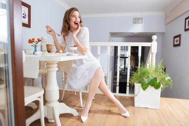 Szczęśliwa atrakcyjna młoda kobieta w białej sukni i butach siedzi i je deser w kawiarni