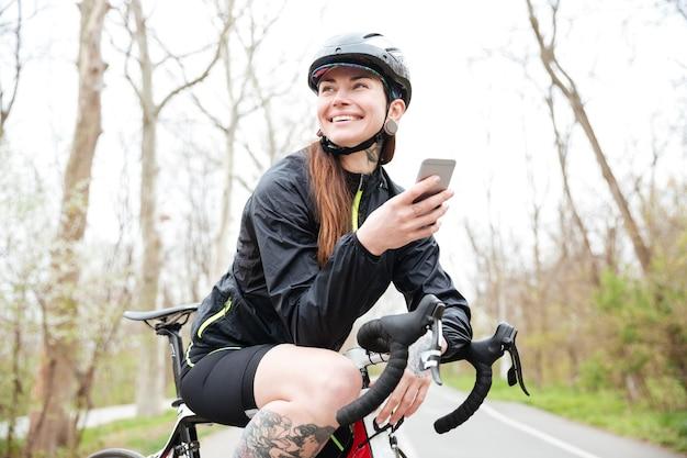 Szczęśliwa atrakcyjna młoda kobieta w kasku rowerowym na rowerze za pomocą smartfona