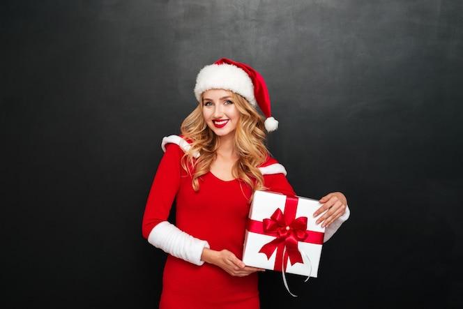 Szczęśliwa atrakcyjna młoda kobieta w stroju świętego mikołaja trzymająca obecne pudełko nad czarną powierzchnią