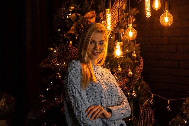 Szczęśliwa atrakcyjna młoda kobieta w stylowym niebieskim garniturze z dzianiny pozuje w pokoju na tle drzewa noworocznego z jasnymi pięknymi światłami i girlandami