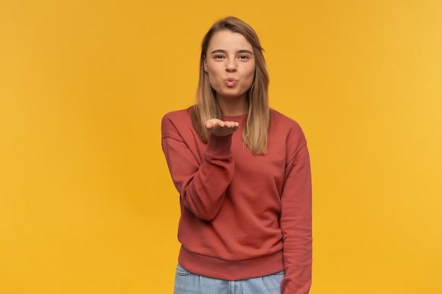 Szczęśliwa atrakcyjna młoda kobieta w ubranie stojąc i wysyłając pocałunek na żółtej ścianie