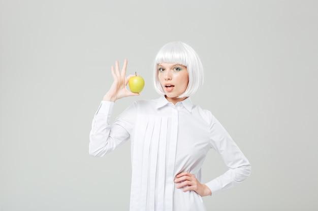 Szczęśliwa atrakcyjna młoda kobieta z blond włosami trzymająca świeże jabłko