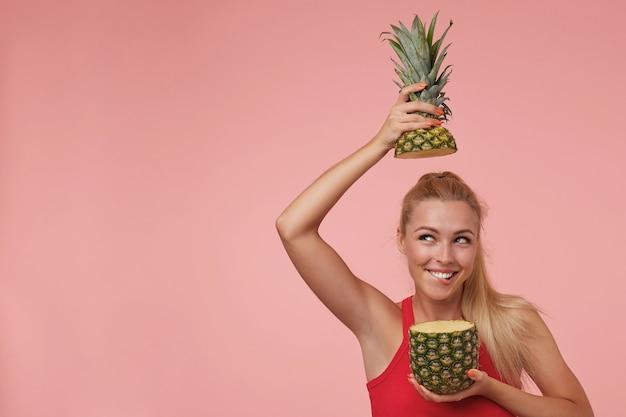 Szczęśliwa atrakcyjna młoda kobieta z długimi blond włosami pozuje, patrzy w górę i uśmiecha się, gryzie dolną wargę i bawi się ciętym ananasem