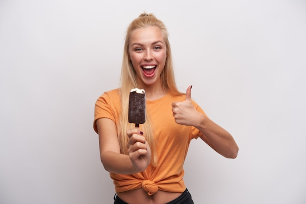 Szczęśliwa atrakcyjna młoda kobieta z długimi blond włosami, trzymając lody w uniesionej dłoni i pokazując kciuk stojąc na białym tle, będąc w duchu i uśmiechając się szeroko