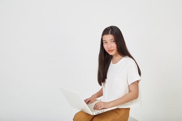 Szczęśliwa atrakcyjna młoda kobieta z laptopem siedząca ze skrzyżowanymi nogami i patrząca na pustą przestrzeń na białym tle studia