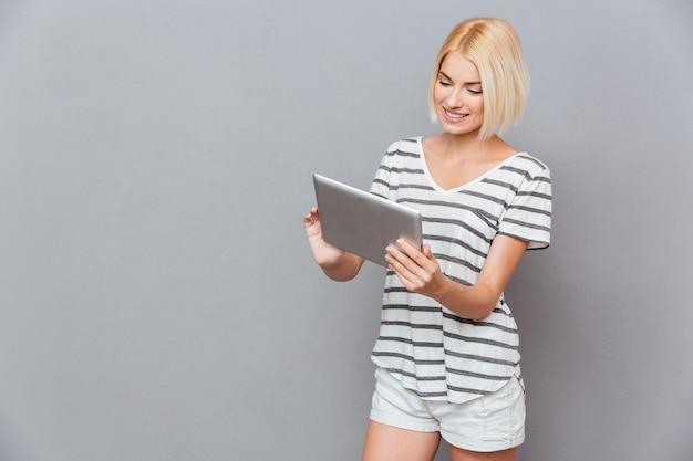 Szczęśliwa atrakcyjna młoda kobieta za pomocą tabletu