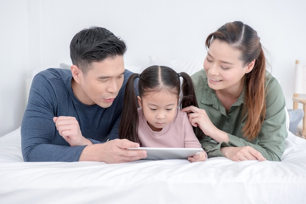 Szczęśliwa atrakcyjna młoda rodzina ogląda pastylkę