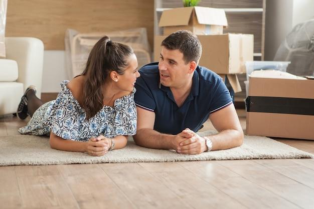 Szczęśliwa atrakcyjna para leżąca na podłodze w swoim nowym mieszkaniu