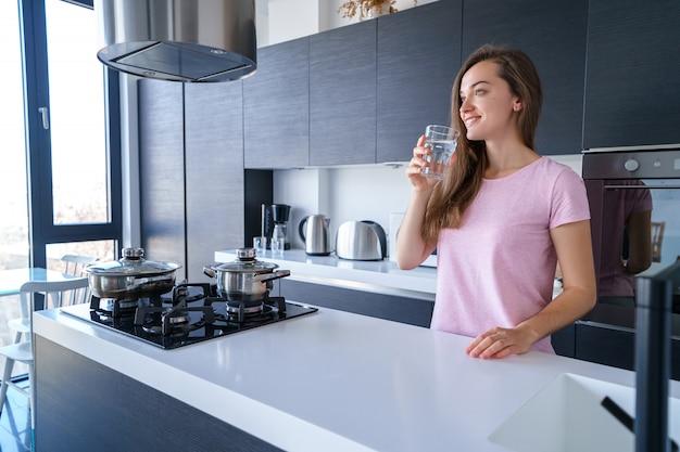 Szczęśliwa atrakcyjna radosna brunetki kobieta pije świeżą czystą filtrującą oczyszczoną wodę w kuchni w domu. zdrowy styl życia i ugasić pragnienie