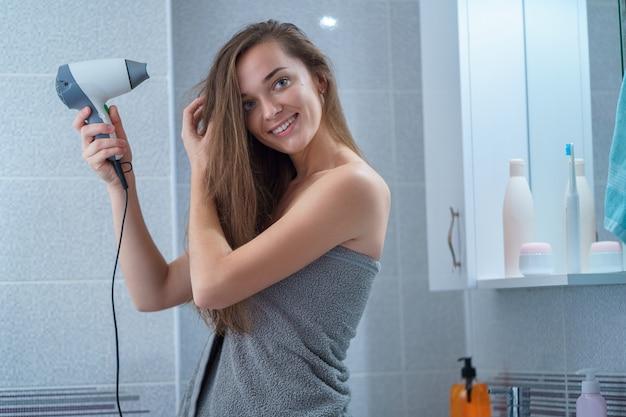 Szczęśliwa atrakcyjna radosna brunetki kobieta w ręczniku suszy włosy z suszarką do włosów w łazience po prysznic w domu