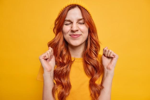 Szczęśliwa atrakcyjna rudowłosa dziewczyna ma zamknięte oczy, zaciska pięści, oczekuje pozytywnych wyników, spodziewa się czegoś niesamowitego, ubrana w żółte ubrania pozy, w pomieszczeniu uzyskała aprobatę, cieszy się z sukcesu